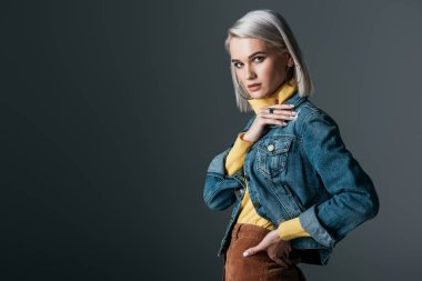 attractive girl in yellow turtleneck and fashionable jeans jacket, isolated on grey