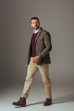 stylish man posing in beige pants and autumn tweed jacket, on grey