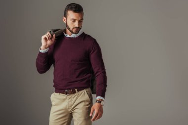 stylish handsome man posing in burgundy sweater with jacket on shoulder, isolated on grey
