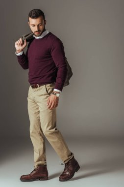 fashionable man posing in beige pants and burgundy sweater with autumn jacket on shoulder, on grey