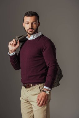 fashionable bearded man posing in burgundy sweater with autumn jacket on shoulder, isolated on grey