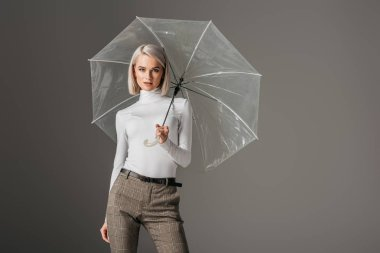 elegant model in white turtleneck with transparent umbrella, isolated on grey
