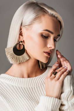 elegant blonde model posing in white sweater and big round earrings, isolated on grey