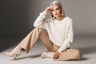 """Картина, постер, плакат, фотообои """"привлекательная модная женщина, позирующая в белом модном свитере, бежевых брюках и на осенних каблуках, на сером """", артикул 206432966"""