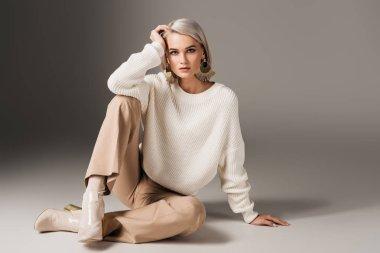 elegant beautiful girl posing in white sweater and autumn heels, on grey