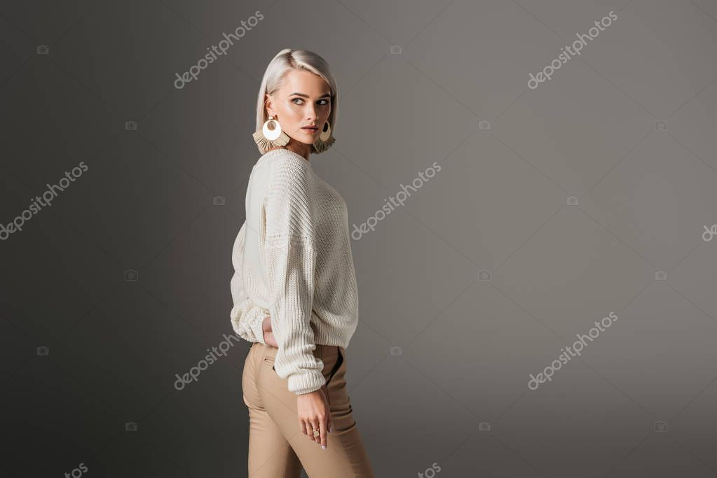 Attractive girl posing in white sweater, isolated on grey stock vector
