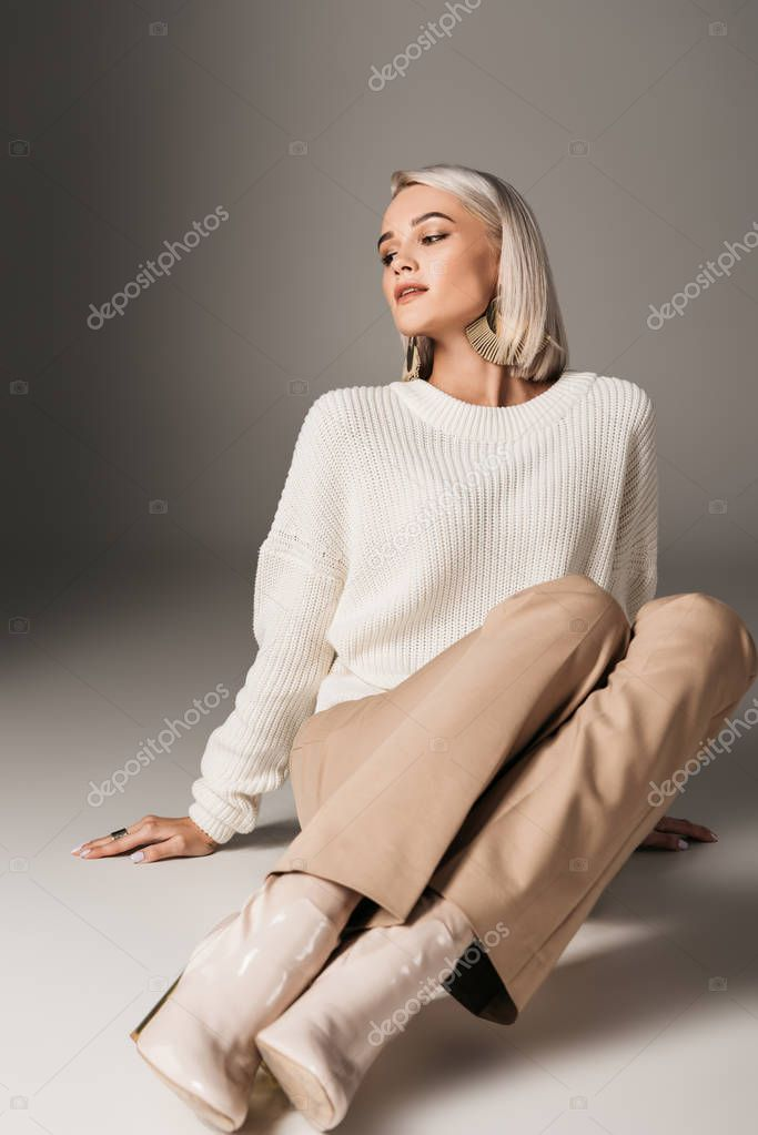 Fashionable beautiful girl posing in white sweater, beige pants and trendy autumn heels, on grey stock vector