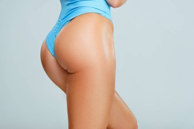 Cropped image of sexy female buttocks in blue swimwear isolated on grey
