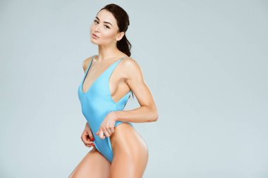 sexy sportive woman touching blue swimwear and looking at camera isolated on grey