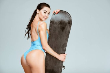 back view of sexy snowboarder in blue swimwear posing with snowboard isolated on grey