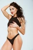 sexy žena dotýká sportovní podprsenku a při pohledu na fotoaparát izolované Grey