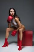 sexy sportliche Frau in weißer Badebekleidung und Boxhandschuhen sitzt auf rotem Würfel auf grau