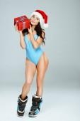 sexy Sportlerin in blauer Sportbekleidung und Weihnachtsmütze mit Geschenk isoliert auf grau