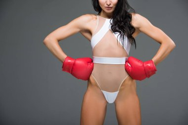 cropped image of sexy sportive woman in white leotard and boxing gloves standing with hands akimbo isolated on grey