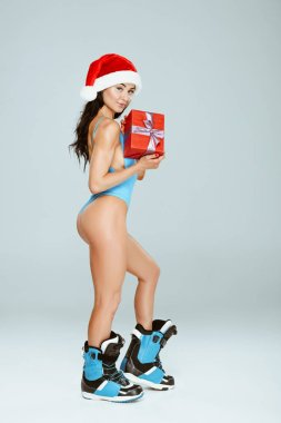 side view of sexy sportive woman in blue swimwear and snowboard boots holding gift isolated on grey
