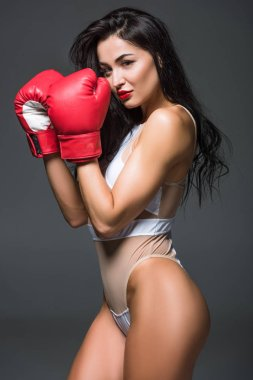 side view of sexy sportive woman in white sportswear and boxing gloves looking at camera isolated on grey