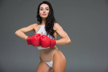 sexy sportive woman in white leotard showing hands in boxing gloves isolated on grey
