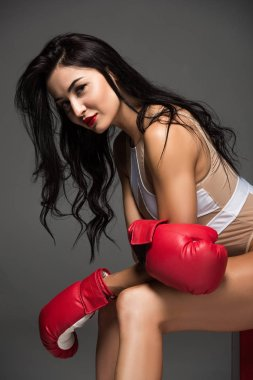 side view of sexy sportive woman in white swimwear and boxing gloves sitting isolated on grey