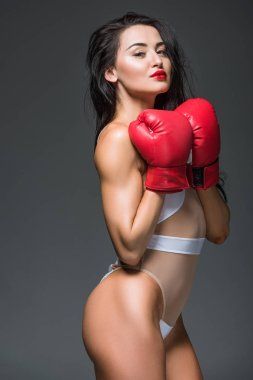 side view of sexy sportive woman in white swimwear and boxing gloves isolated on grey