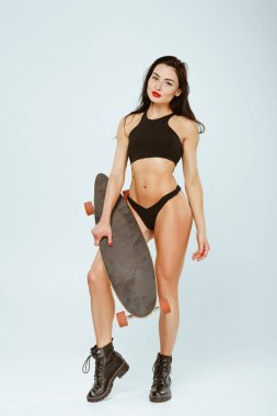 sexy woman in sport bra and panties standing with skateboard isolated on grey