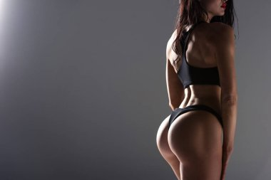cropped image of seductive woman in sport bra and panties isolated on grey
