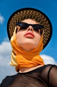 bottom view of stylish girl in trendy sunglasses and hat