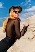 Fotografie krásná mladá žena pózuje v elegantní hat blízko písečné duny