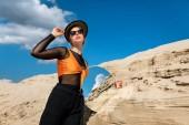 Fotografie módní model představuje s kulaté zrcadlo poblíž dune