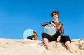 Fotografia modello alla moda che propone con specchi rotondi con la riflessione del cielo blu