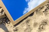pohled shora zrcadlo s odrazem modré oblohy oblačnosti, leží na písku
