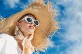 gyönyörű lány pózol divatos napszemüveg, a selyem sál és a szalma kalap