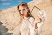 attractive blonde girl with white silk scarf walking on sand dune