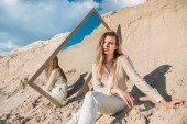Fotografie elegant young woman posing in white clothes near mirror on sand
