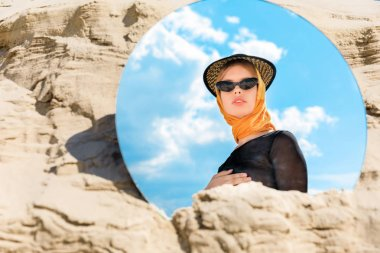 round mirror with reflection of beautiful stylish model in hat and sunglasses