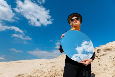 stylish attractive girl posing with round mirror and reflection of cloudy sky