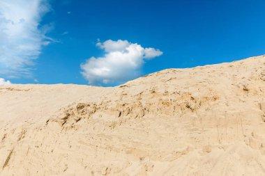 Manzaralı kumul, mavi gökyüzü ve bulutlar