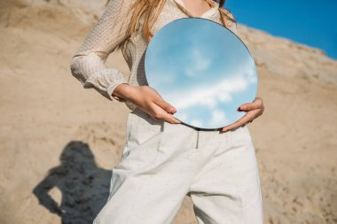 cropped view of stylish girl holding mirror with reflection of blue sky with clouds