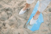 Fotografie partial view of model standing on sand and piece of mirror with reflection of blue sky