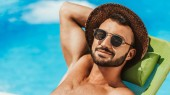 Fotografie gut aussehender Mann mit Sonnenbrille und Strohhut auf Liegestuhl am Pool Sonnen