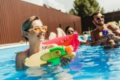 Fotografie happy multiethnic friends playing with water guns in swimming pool