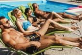 napozóágyak a medencénél, szelektív összpontosít napozás fürdőruhás multikulturális meg
