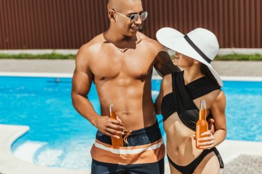 multicultural couple holding bottles of beer and hugging at poolside
