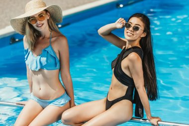 multicultural girls in swimsuits and sunglasses sitting at swimming pool