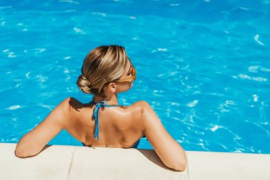 back view of girl in swimsuit and yellow sunglasses relaxing in swimming pool