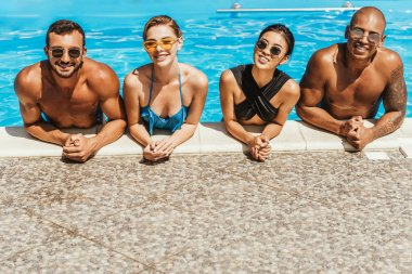 multicultural friends in swimsuits and sunglasses posing in swimming pool