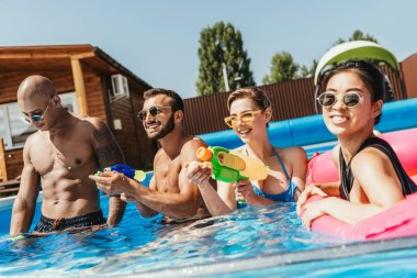 smiling multicultural friends having fun with water guns in swimming pool