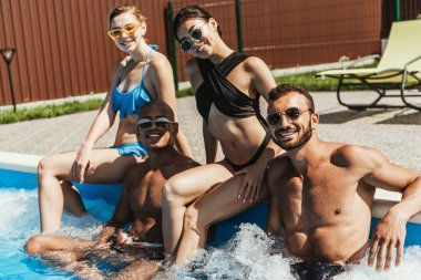 smiling multiethnic friends in swimsuits and sunglasses relaxing at poolside
