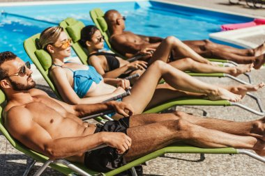 multicultural friends in swimsuits sunbathing on sunbeds at poolside, selective focus