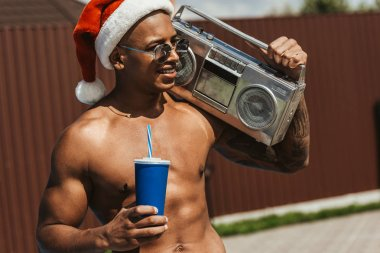 smiling african american man in santa hat with drink and retro boombox