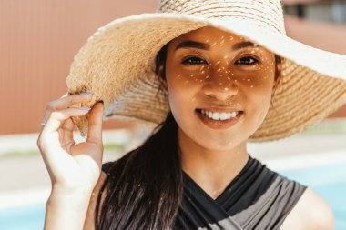 happy asian girl in swimsuit and straw hat